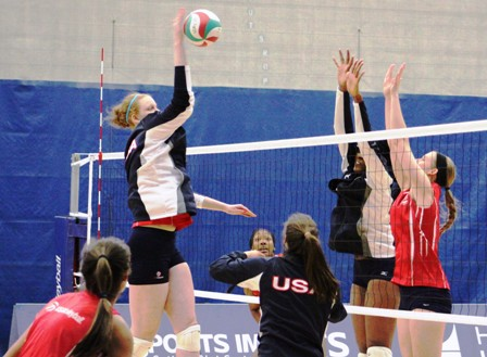 Katie Slay hitting over blockers in a demonstration my members of the USA Volleyball Women's National Team.
